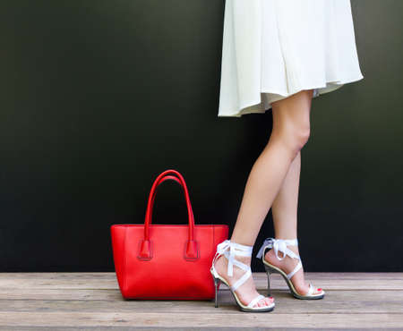 Fashionable woman with long beautiful legs in Ribbon Tie Stilleto shoes standing on the black background. Short white dress. Girl stands next to large red handbag. Part of body. Fashion and Style. Banque d'images