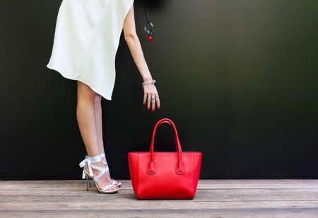 Shopping. Het meisje trekt haar hand naar de tas. mode meisje in een korte witte jurk in mooie schoenen met linten en grote rode handtas op een zwarte achtergrond. Deel van het lichaam.