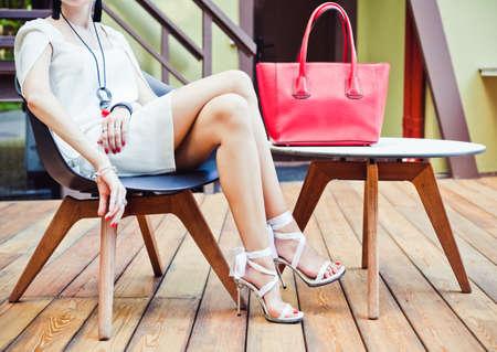 ファッションとスタイル。女の子の大きな赤い超ファッショナブルなハンドバッグの短い白のドレスで夏のカフェに座って高かかとの暖かい夏の夜 写真素材