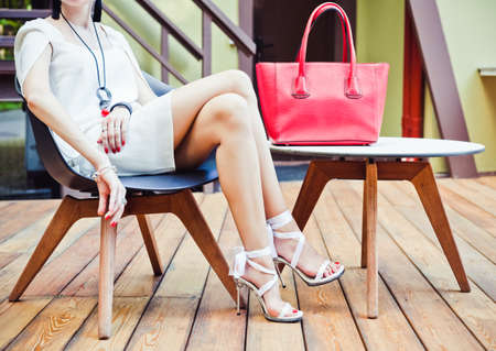 Fashion and Style. Girl sitting of summer cafe with a big red super fashionable handbags in short white dress and high heels on a warm summer evening. Warm colors