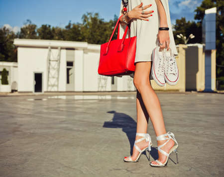leggy girl: Fashion and style. Leggy girl stands in a park on a summer evening in a short white dress and holding a sneakers and big red fashionable handbag Stock Photo