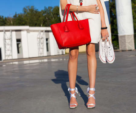 leggy girl: Fashion and style. Leggy girl stands in a park on a summer evening in a short white dress and holding a sneakers and big red fashionable handbag. Part of body. Stock Photo