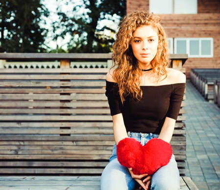 amorousness: love, sadness and loneliness. Beautiful long-haired girl in sad loneliness summer evening. She is holding a big red heart. Broken heart. Warm color.