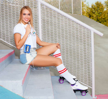 beautiful young blond woman sitting on the stairs in shorts, t-shirt with headphones and a cassette player. The feet high socks and roller skates quads derby. Warm sunny summer evening.