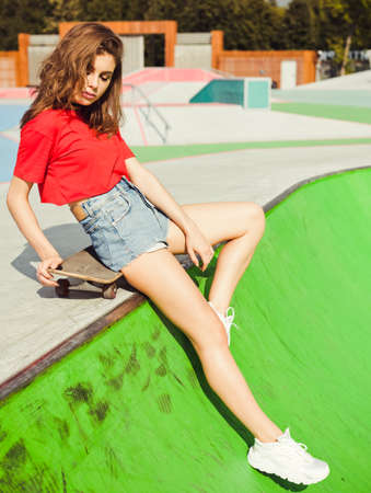 Beautiful young fashionable girl posing in a red T-shirt and denim shorts sitting on a skateboard in the park summer day Stock Photo