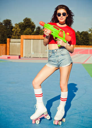 Portrait beautiful sexy girl posing on a vintage roller skates derby in denim shorts, white T-shirt and sunglasses in the skate park with water gun on a warm summer evening and having fun. Outdoor.