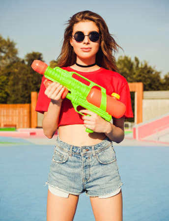 Beautiful sexy girl posing in denim shorts, white T-shirt and sunglasses in the skate park with water gun on a warm summer evening and having fun.