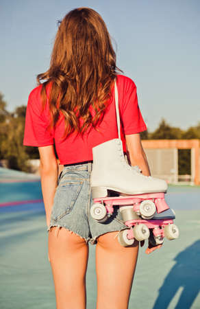 hair roller: Girl with long dark hair is back with roller skates on her shoulder. Warm summer evening in the skate park. Outdoor.