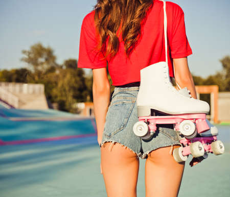 Girl with long redhead hair is back with white roller skates on her shoulder. Warm summer evening in the skate park. Outdoor.