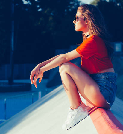 Waiting. Farewell. A girl sits on the ramp skate park in the rays of warm sun. Outdoor, summer. Warm color.