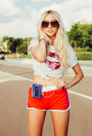 shorts t shirt sexy: Summer fashion stylish portrait of young pretty sexy blonde girl posing in vinage sunglasses, T-shirt, shorts and listening to music with headphones on vintage cassette player. Outdoor. Stock Photo