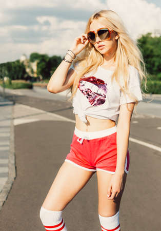 shorts t shirt sexy: Outdoor summer fashion stylish portrait of young pretty sexy blonde girl posing in vinage sunglasses, t-shirt and red shorts.