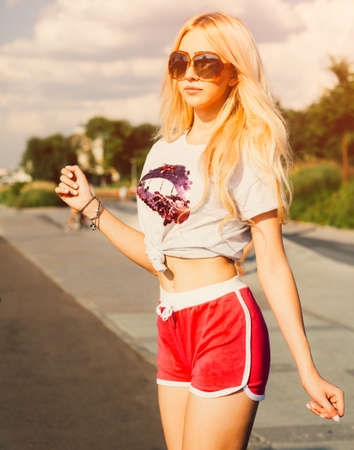 shorts t shirt sexy: Portrait of young sexy woman in Vintage T-shirt, shorts posing on California beach. Solar flare.