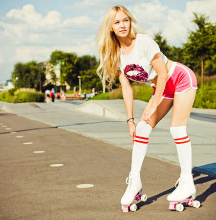 shorts t shirt sexy: Beautiful sexy blonde girl posing on a vintage roller skates in pink shorts and white T-shirt on a warm summer evening. Adjusts her gaiters. Rollers quads derby. Outdoor.