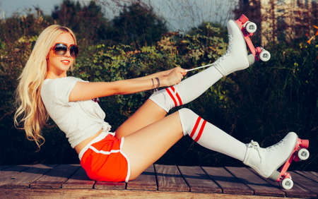 Portrait of a beautiful young blonde girl tighten the laces sitting on a bench in a vintage roller skates, wearing shorts, golfs and a T-shirt. Looking at camera. Hot summer day. Outdoor.