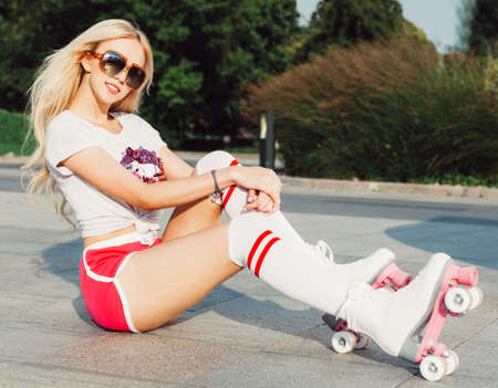 shorts t shirt sexy: A stunner smiling summer closeup portrait of sexy young happy woman posing in a vintage roller skates, sunglasses, T-shirt shorts sitting on a road hot summer day. Outdoor. Stock Photo