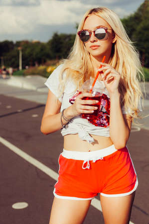 shorts t shirt sexy: Beautiful sexy blonde girl in vintage red shorts and white T-shirt holds a hand a glass of fresh cool summer drink. summer vacation in the heat, freshness.