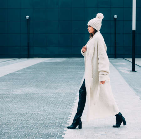 Fashionable stylish Looker girl in white cap and knit coat. Walks on the Europe street. Outdoor. Streetstyle. Banque d'images