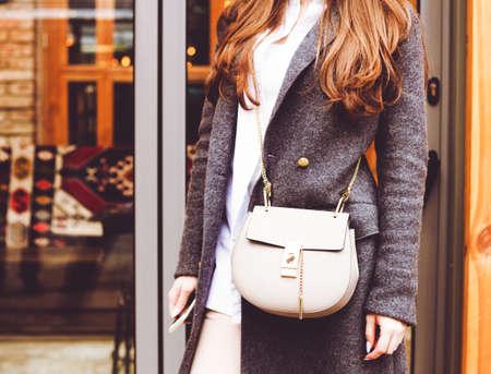 ファッションと美容。ハンドバッグと女の子のグレーのコート。クローズ アップ、ストリート スタイル。