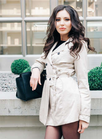 Fashionable brunette girl with long hair dressed in a raincoat, with black hand bag posing near a boutique in Italy. Streetstyle. Fashion. Outdoor.