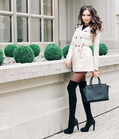 Long-legged brunette girl with long hair, dressed in a raincoat, high black high-heeled boots with a handbag posing near a boutique in the European city Stock Photo