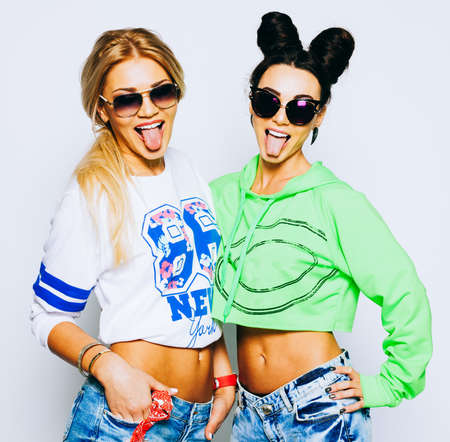 Indoor fashion lifestyle portrait of pretty teen happy friends girls, hugs, wearing bright outfits, brunette and blonde hairs, make up, trendy accessory, sunglasses showing long tongue, crazy. Banque d'images