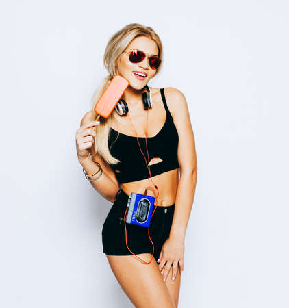 Breathtakingly beautiful sexy girl blonde posing in a black outfit, sunglasses with an ice cream ice-cream and a vintage cassette player and headphones. Rest and enjoyment. Indoor. Stock Photo