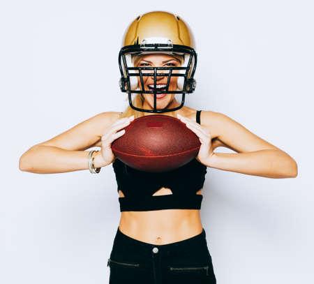 ヘルメット黒服のポーズとボールを保持している頭の上で信じられないほど美しい運動のブロンドの女の子。スポーツ。一致します。アメリカン フ