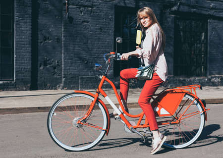 Beautiful long-haired young blonde woman enjoys an ice cream sitting on a red vintage bicycle on the street.