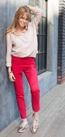 brogues: Portrait of a young woman dressed in a blouse, red Chino Trouser, and gold brogues. Posing next to a gray wall. Fashion. Streetstyle.