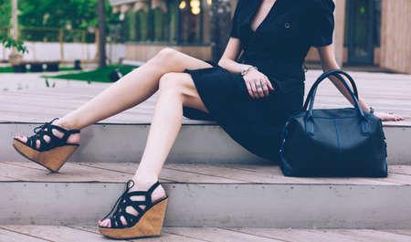 Chica sentada en las escaleras con un gran bolso negro súper de moda con un vestido y sandalias de tacón alto en una cálida noche de verano. Parte del cuerpo. Al aire libre.