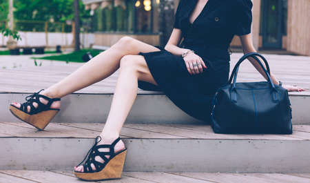 Girl sitting on the stairs with a big black super fashionable handbags in a dress and High Wedge Sandals on a warm summer evening. Part of body. Outdoor.