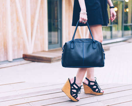 Fashion. A girl in a black dress and with a fashionable handbag is standing on the veranda of a summer cafe. Part of body.
