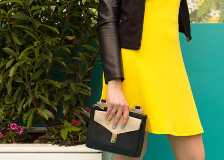 Portrait girl with in a short yellow dress, with a black handbag makes shopping. Part of body. Europe city. Streetstyle.