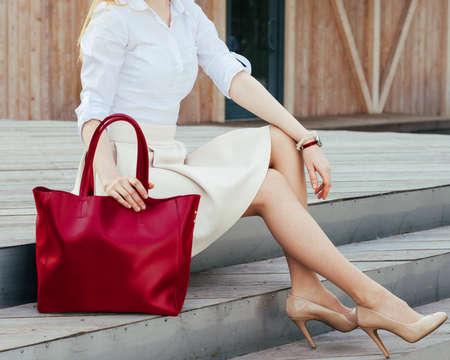 Een deel van het lichaam. Meisje, zittend op de trap met een grote rode super modieuze handtas in een jurk en Wide Fit puntige hakken op een warme zomeravond. Mode.