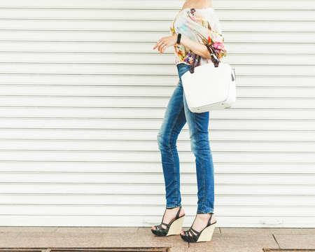 Chiuda in su della borsa di cuoio femminile alla moda all'aperto. Borsa femminile costosa alla moda e di alto stile. Concetto di moda borsa di vendita. Parte del corpo. Sullo sfondo di tavole bianche. Sandali con zeppa alta. Archivio Fotografico