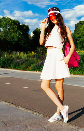 Beautiful sexy asian girl posing on a vintage roller skates in outfit, sneakers and fashionable red Brim Visor Hat on a warm summer evening. Outdoor.