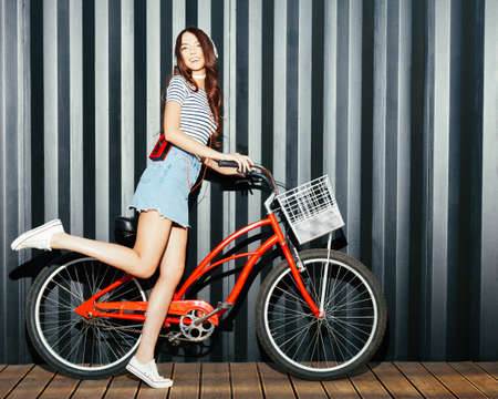 Loker long legged girl asian in a summer outfit, sneakers, cassette player and headphones posing and having fun with a vintage red bicycle. Night shot. Outdoor. Stock Photo