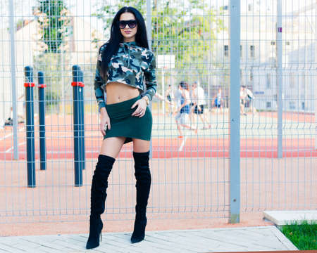 Camouflage. Fashion on the street. Beautiful brunette girl in short skirt khaki high black high heeled boots and super fashionable sunglasses. Stock Photo