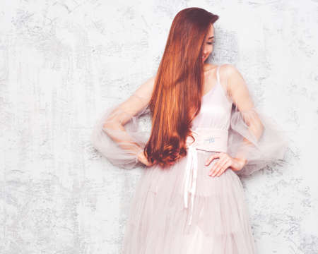 Portrait of a long-haired red-haired girl posing against a gray stone wall in a beautiful airy pink dress. Indoor. Stockfoto