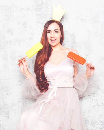 A beautiful young girl in a chic pink airy dress, in a golden crown on her head enjoying ice cream, rejoices and laughs. A princess. Indoor. 写真素材