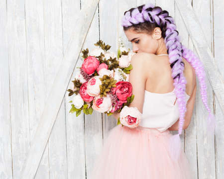 A young girl in a light outfit stands her back with flowers. Hairstyle with colored braids. Indoor. Stock Photo
