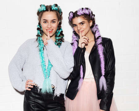 Sign silence. Having fun. Two girls with bright colored braids in fashionable outfits on a light background of a wall in a leather outfit. Indoor. Stock Photo