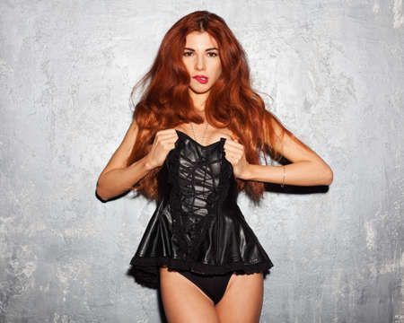 Incredible redhead with long developing hair a young woman in a black leather corset. Indoor.