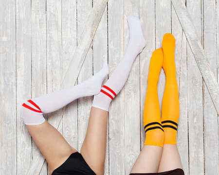 Part of body. Two girlfriends lie on the bed feet up in bright colored socks up. Female friendship. Indoor.