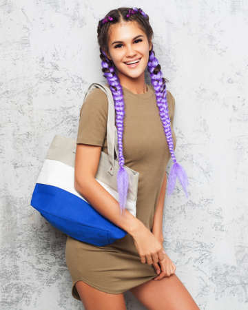 Beautiful girl with purple braids in a trendy outfit and a large handbag on her shoulder smiling looking directly into the camera