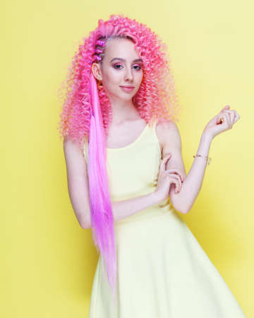 Beautiful pink-haired curly-haired girl posing in the studio on a ghost background. Indoor.