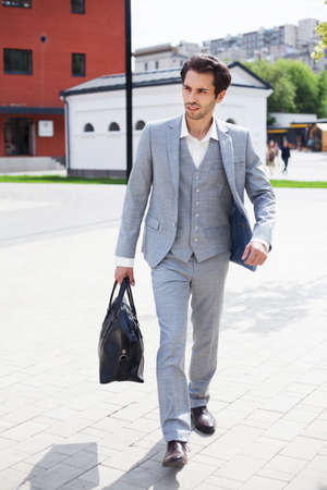 A young businessman in a fashionable gray suit with a large black bag hurries to the office in the morning. Fashion and business. Outdoor.
