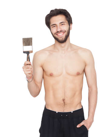 A young bearded male painter holding a brush in his hand, shirtless. Isolation.