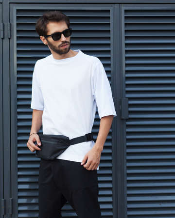 Fanny pack, bum bag. Men's street youth fashion. Young hipster man in sunglasses with a beard posing in the street on a background of roller shades blinds. White T-shirt and black shorts.